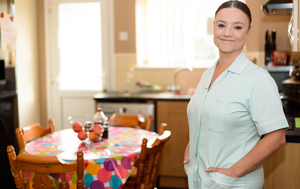 A key worker nurse standing in her kitchen