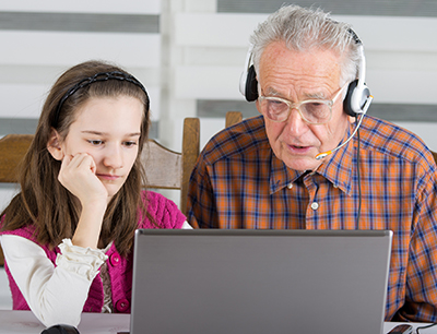Image: An older man with his granddaughter using a computer
