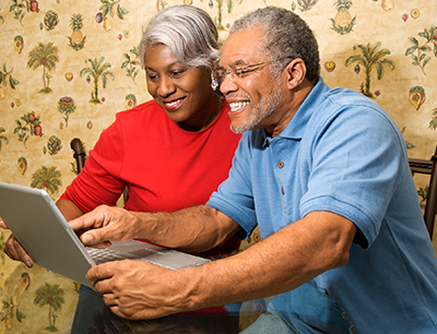 Image: An older couple Skyping their friends and family using their laptop computer