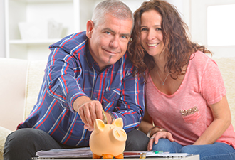 image: a couple holding a piggy bank
