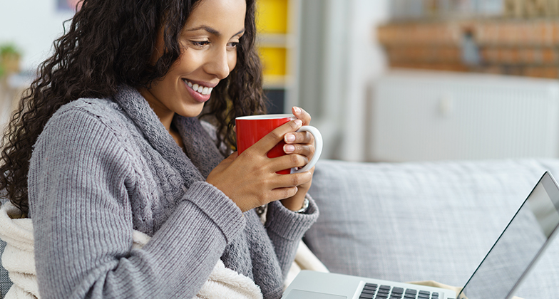 Image: woman in jumper looking at computer
