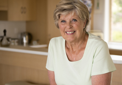 Image: A woman smiling in her kitchen at one of our bungalows for over 55s