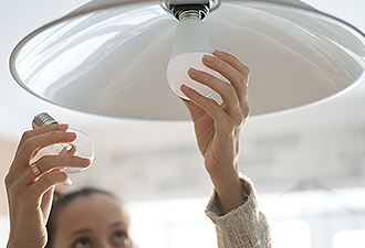 image: woman changing a light bulb