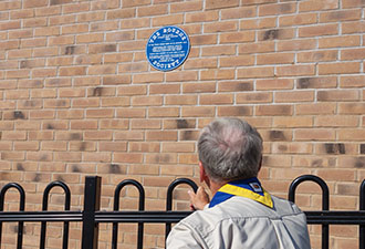 IMAGE: A Scout Leader looks at the plaque